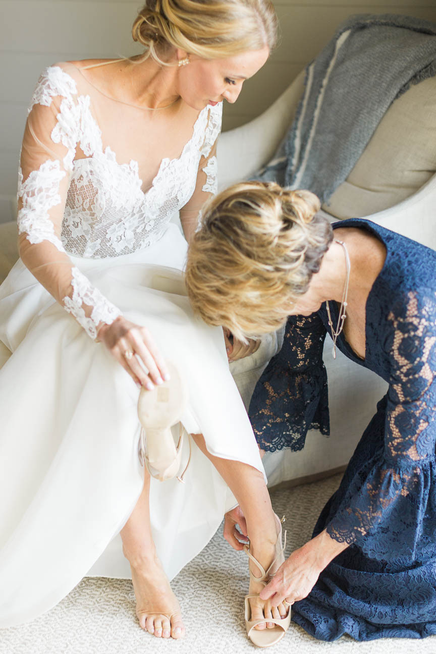 bride's mother helps put her shoes on
