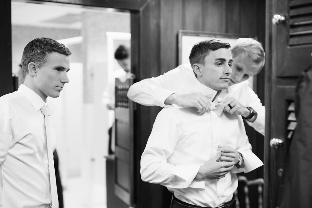 friend helps the groom tie his bowtie in Linville NC