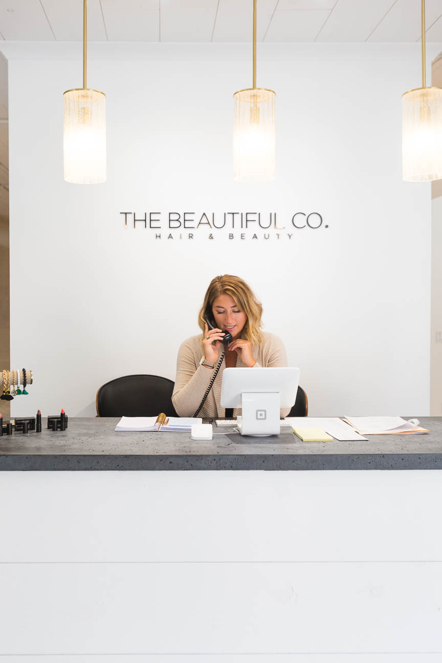 Hostess works at the front desk of The Beautiful Co. salon