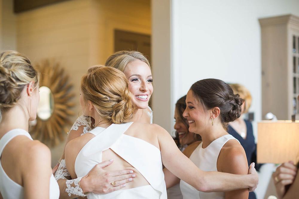 bridesmaids hug bride on wedding day