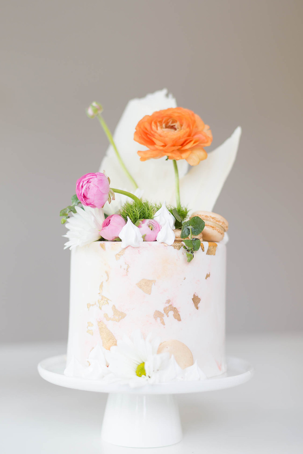 tiny wedding cake with orange ranunculus and white chocolate, golf foiled decorations, creative cakes