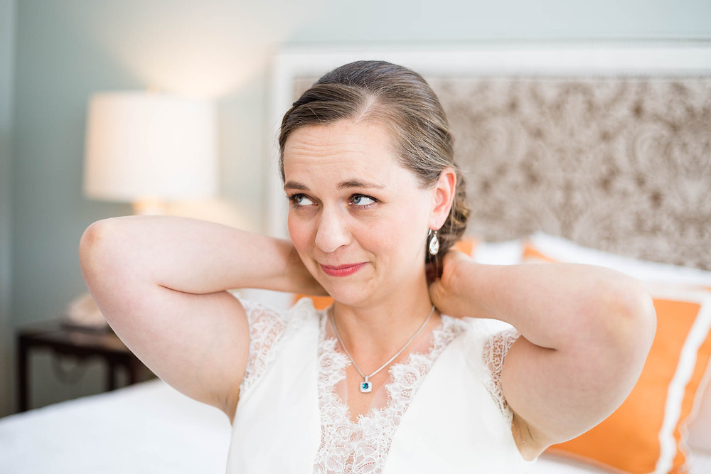 bride puts on David Yearn necklace that the groom gave her on the wedding day