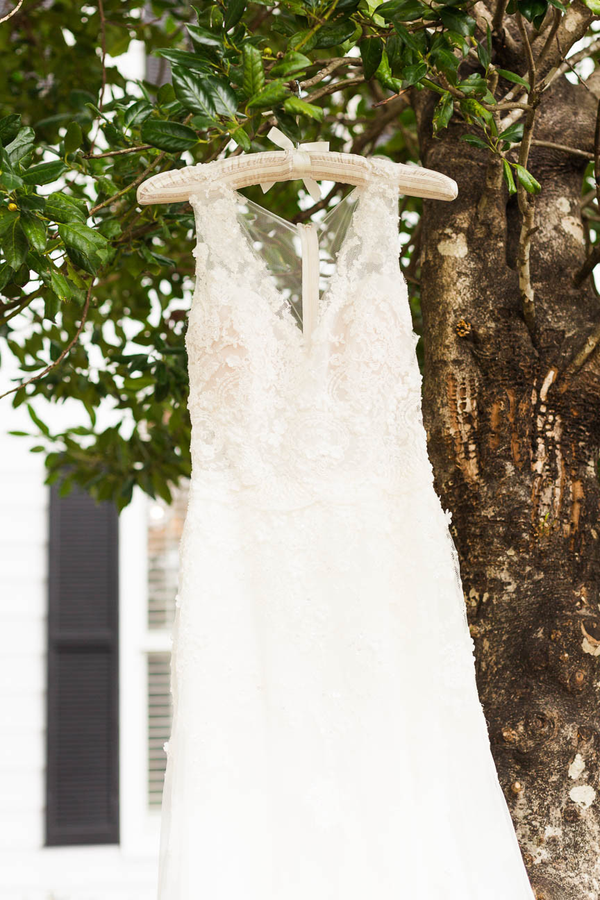 white lace wedding dress hanging from tree on her wedding day
