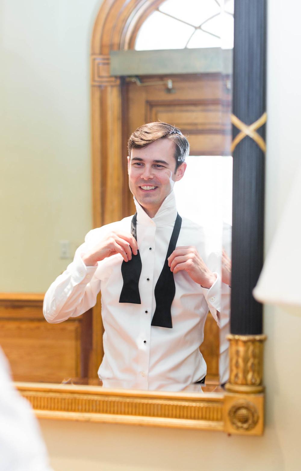 groom ties his bowtie in a mirror before his wedding