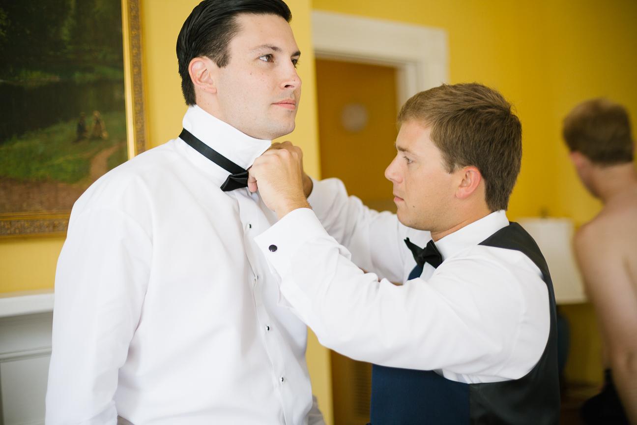 Friends help groom get dressed
