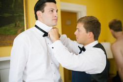 Friends help groom get dressed