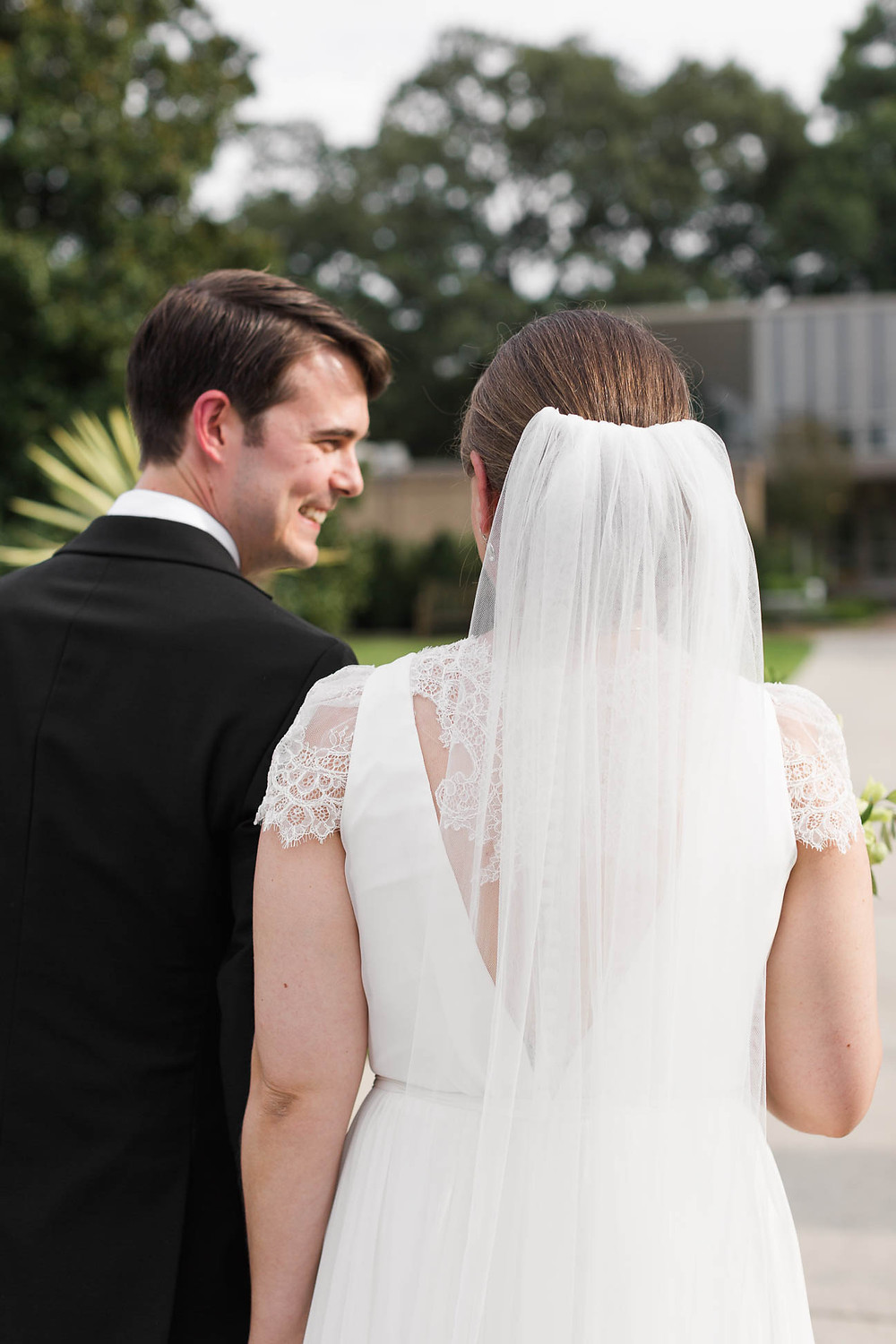 groom smiles back at his bride after the ceremony