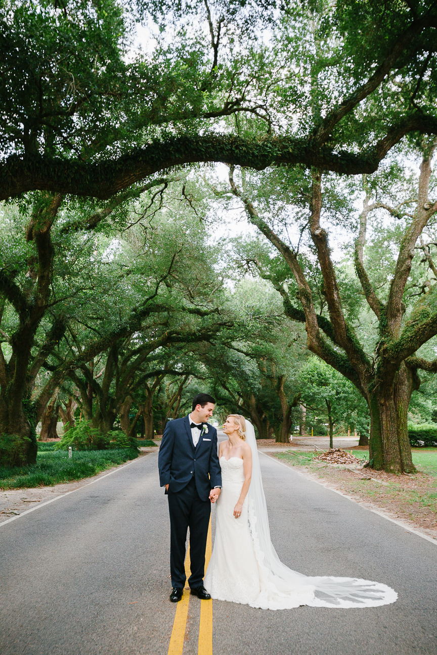 Couple stands under tall trees