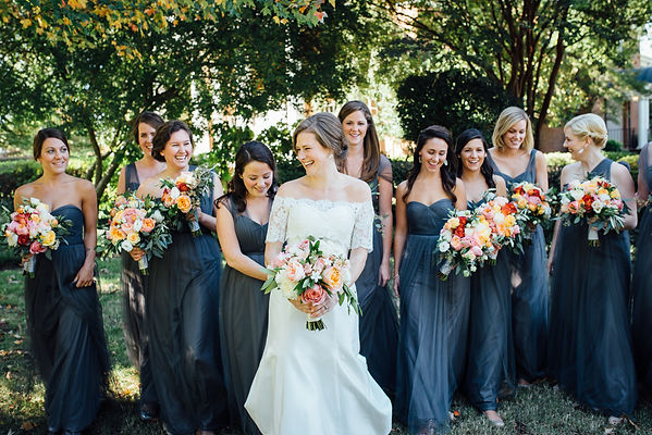Image of a bride walking and  laughing with her bridesmaids before her Memphis, TN wedding ceremony.