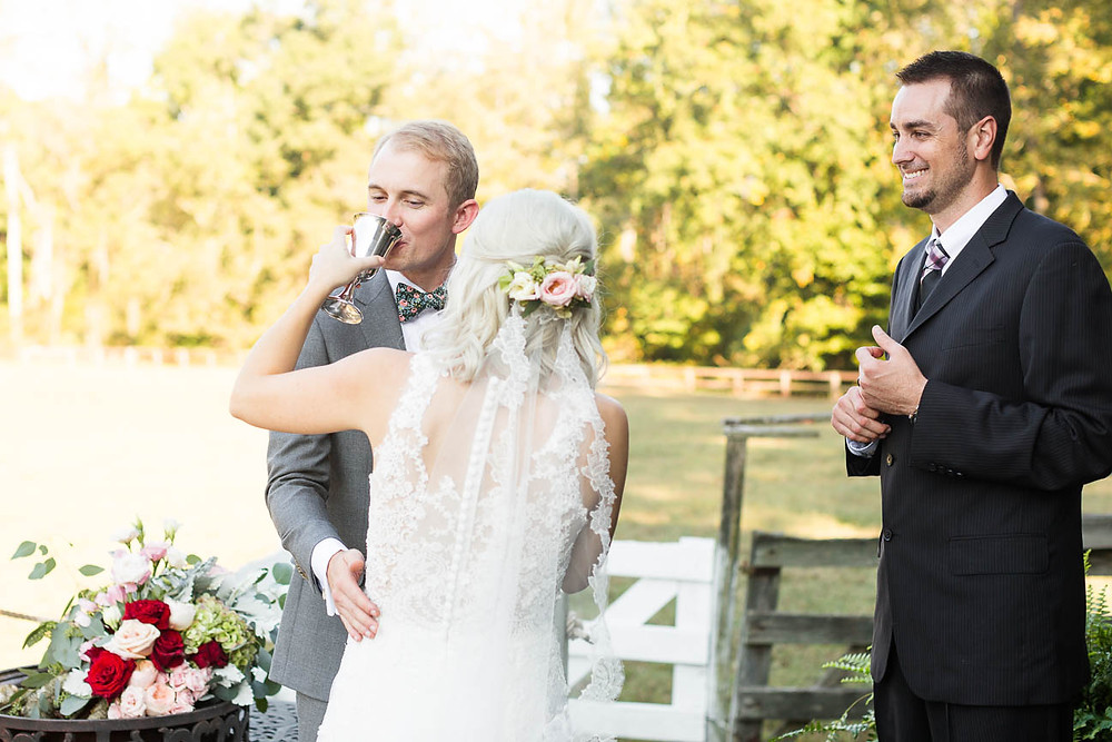 bride gives communion wine to groom on wedding day