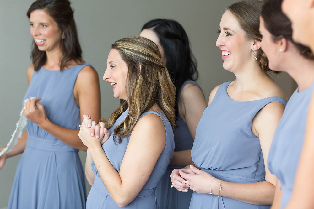 bridesmaids smiles as they see the bride in her dress on the wedding day