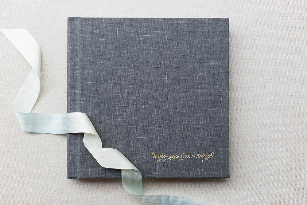 grey linen album with gold names and blue ribbon