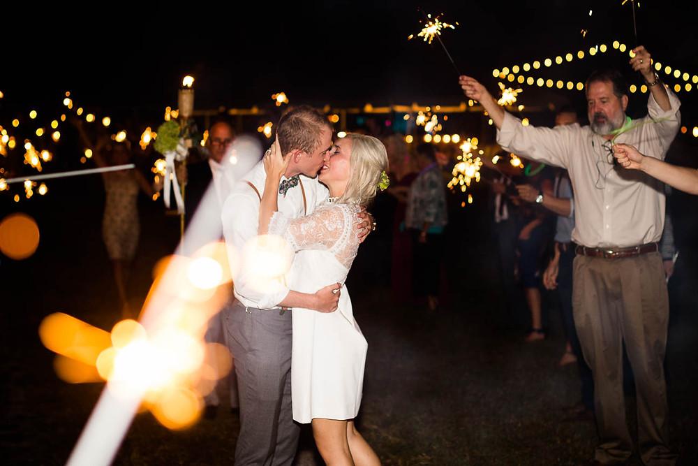 couple kisses during sparkler departure