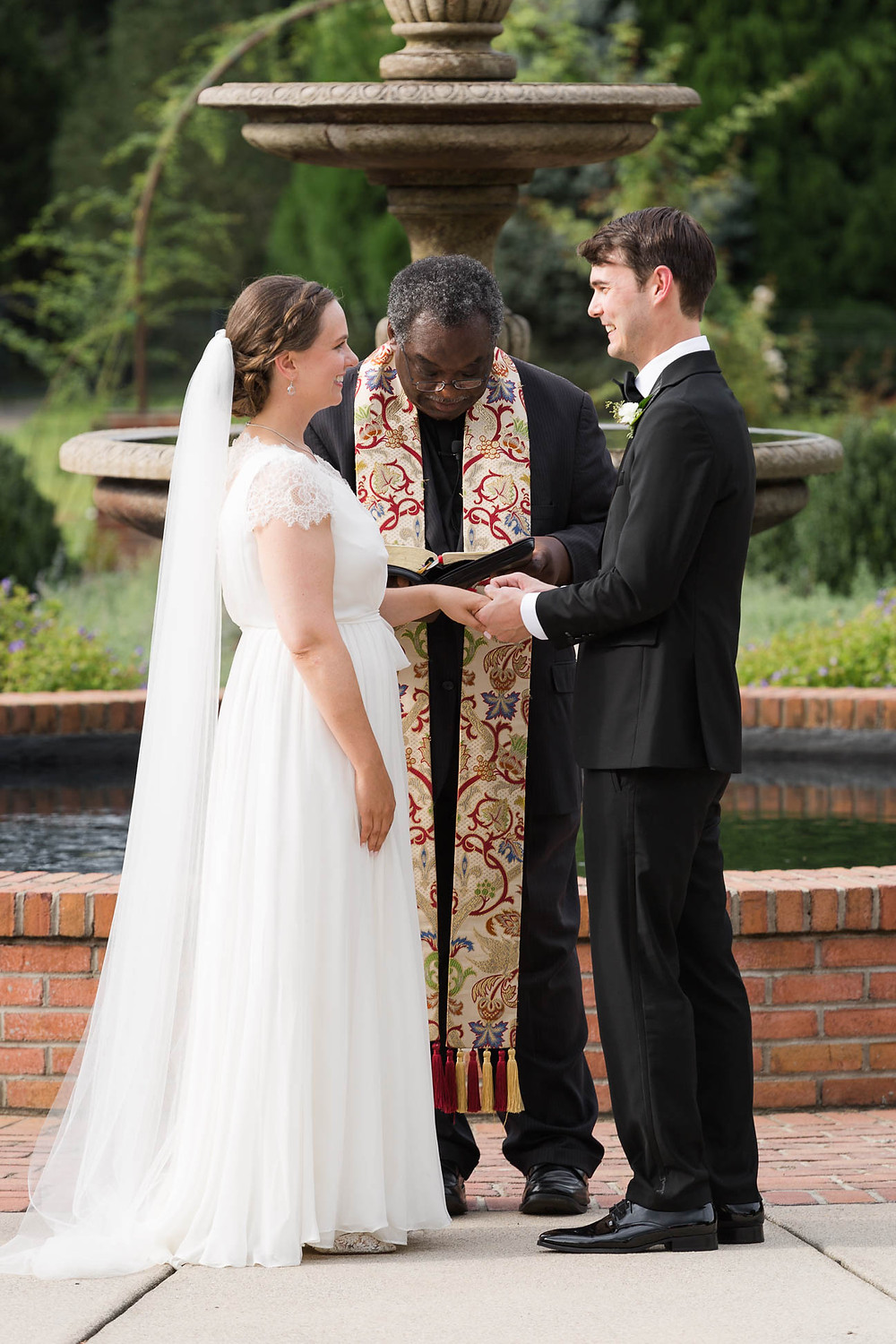 bride and groom exchange vows and rings at outdoor ceremony