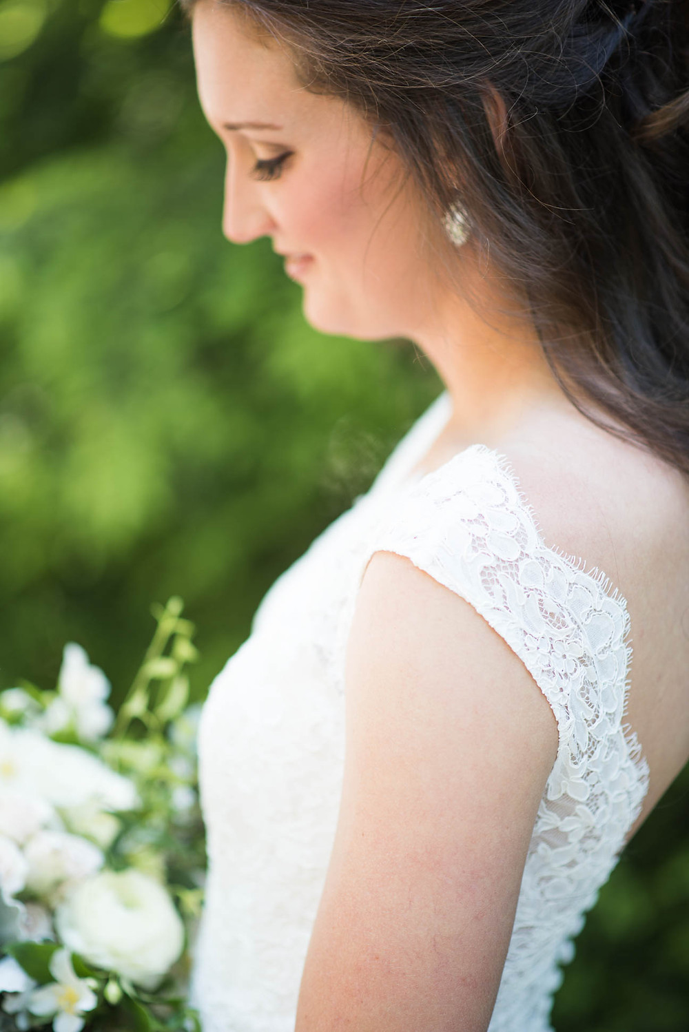 bride looks down at bouquet on the day of her wedding