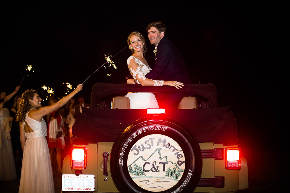 couple leaves their wedding reception in a Jeep Wrangler