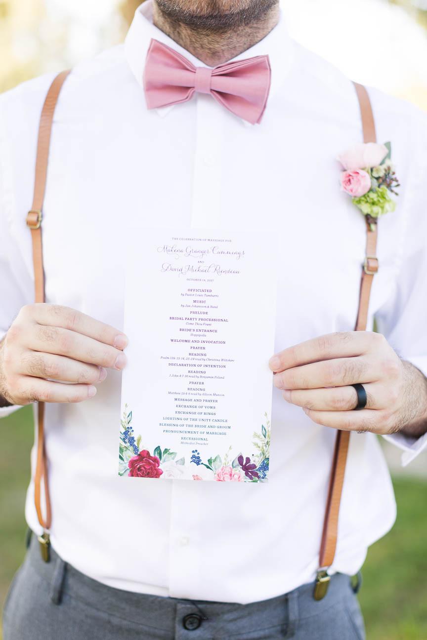 groomsman holding ceremony program