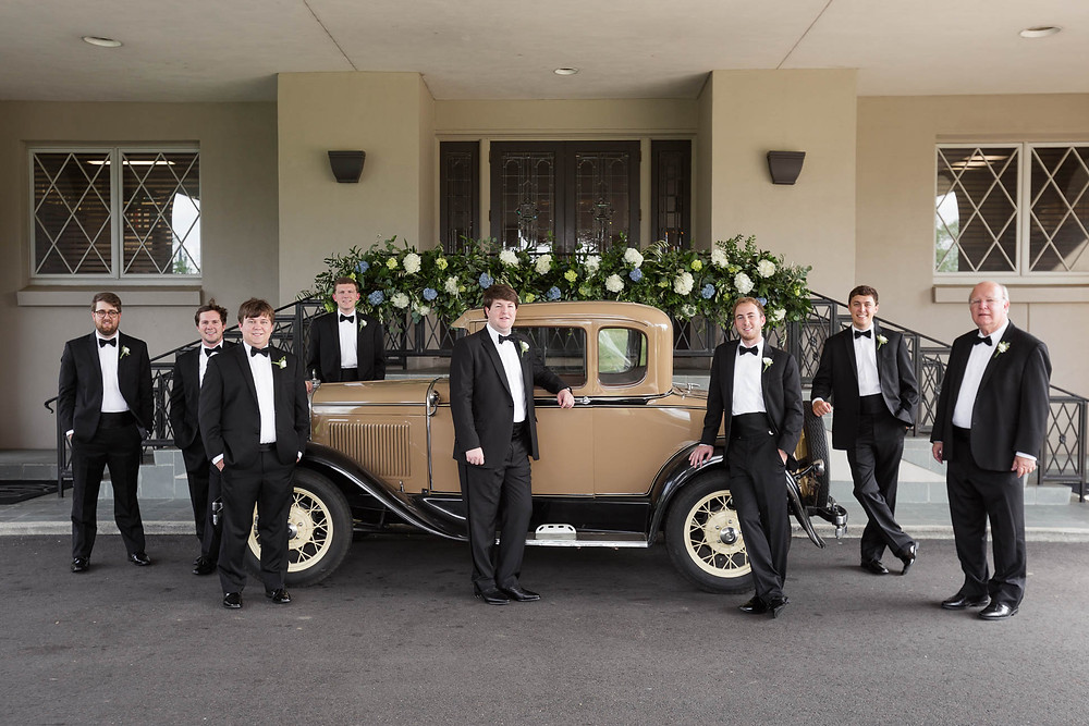 groom and groomsmen stand in front of a family heirloom vintage car
