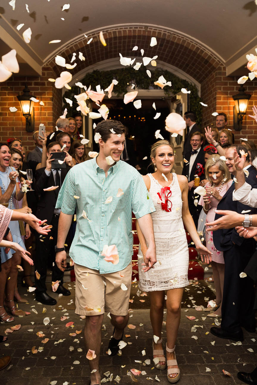 image of guests throwing rose petals as newlyweds leave their wedding