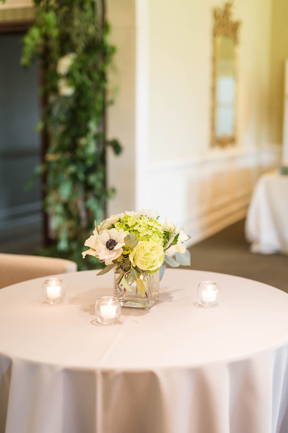 green and white florals on a table at the reception