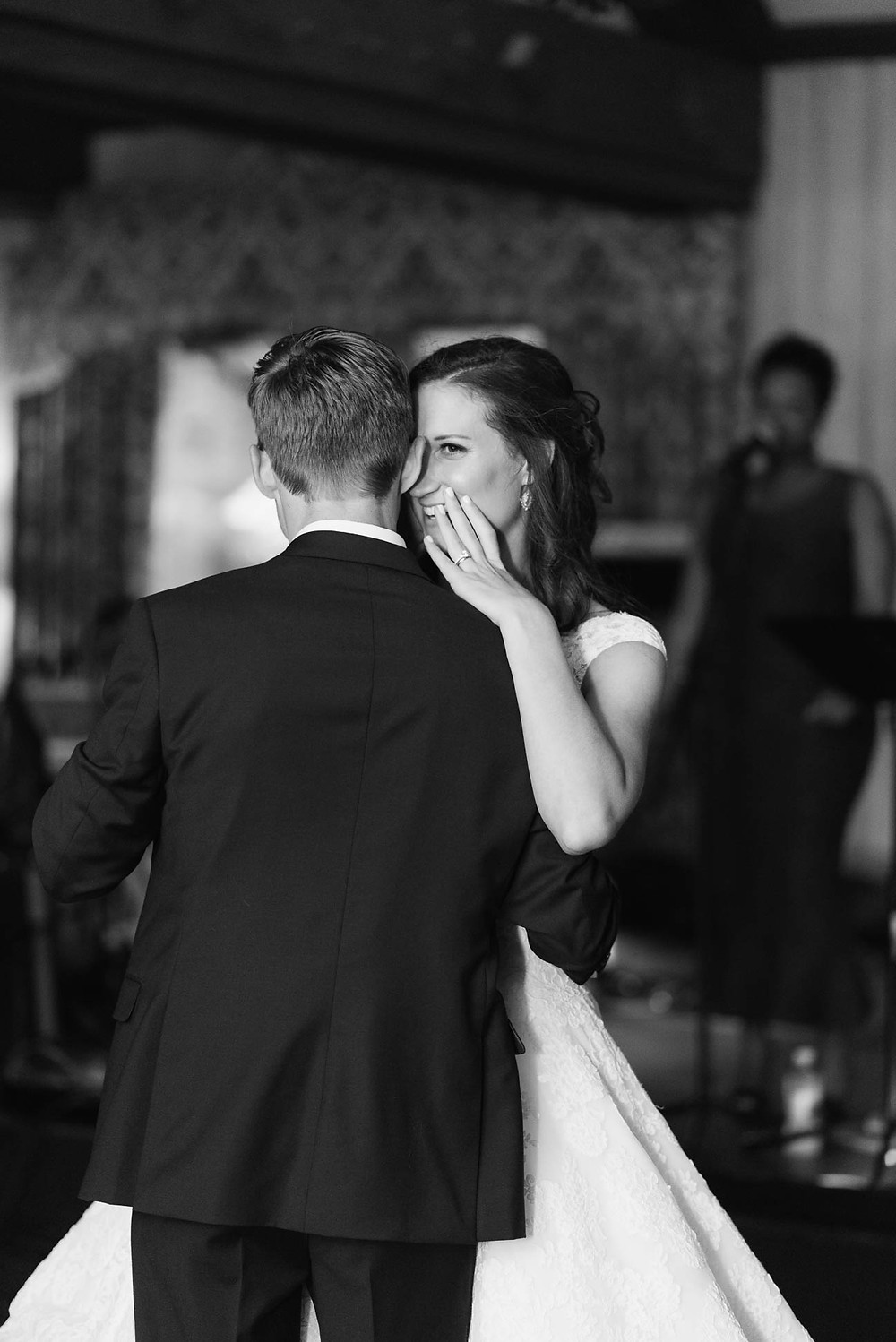 bride whispers into groom's ear during their first dance