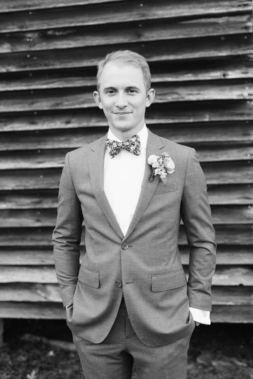 black and white portrait of groom standing in front of tobacco barn