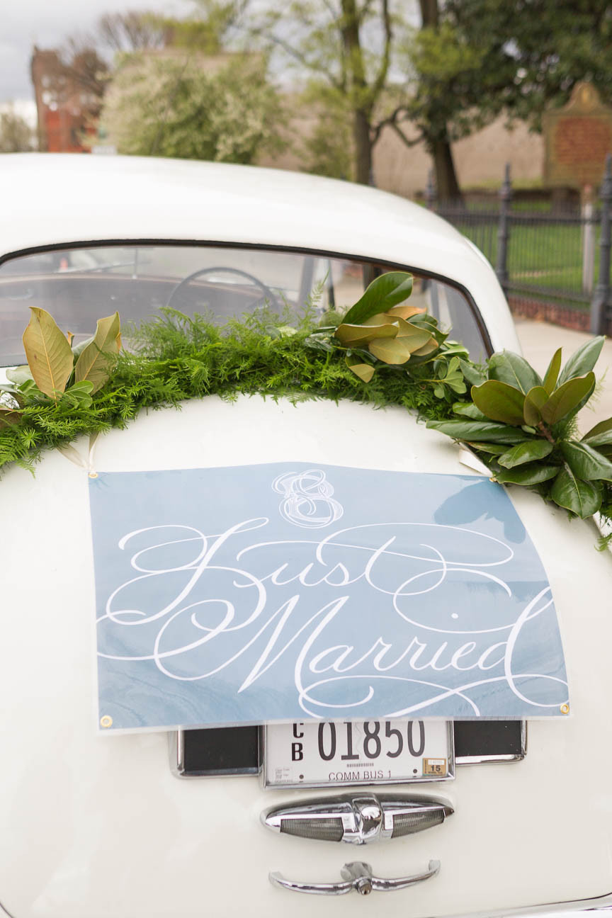 image of newlywed sign on the back of a white vintage car