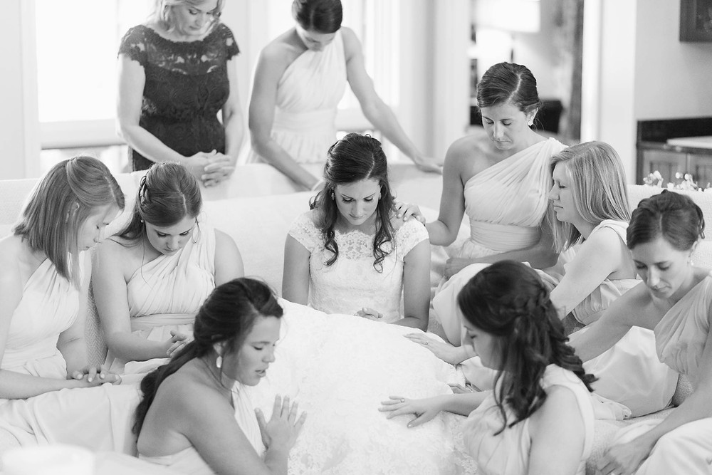 bride's friends pray over her before she walks down the aisle