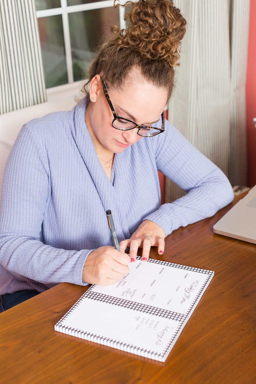 image of designer writing on weekly meal planner