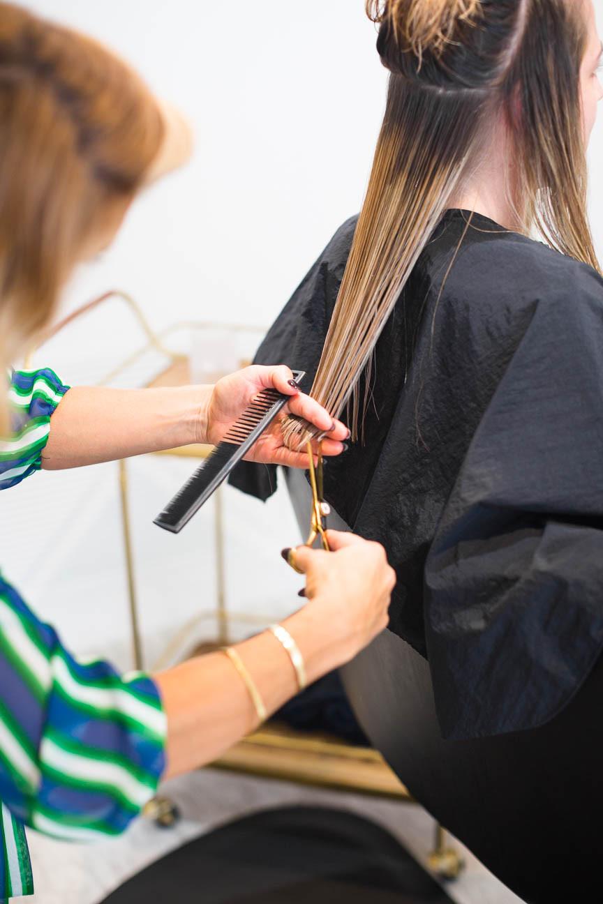 Salon owner trims a girl's hair