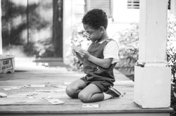 Young Boy Plays on Front Porch Image