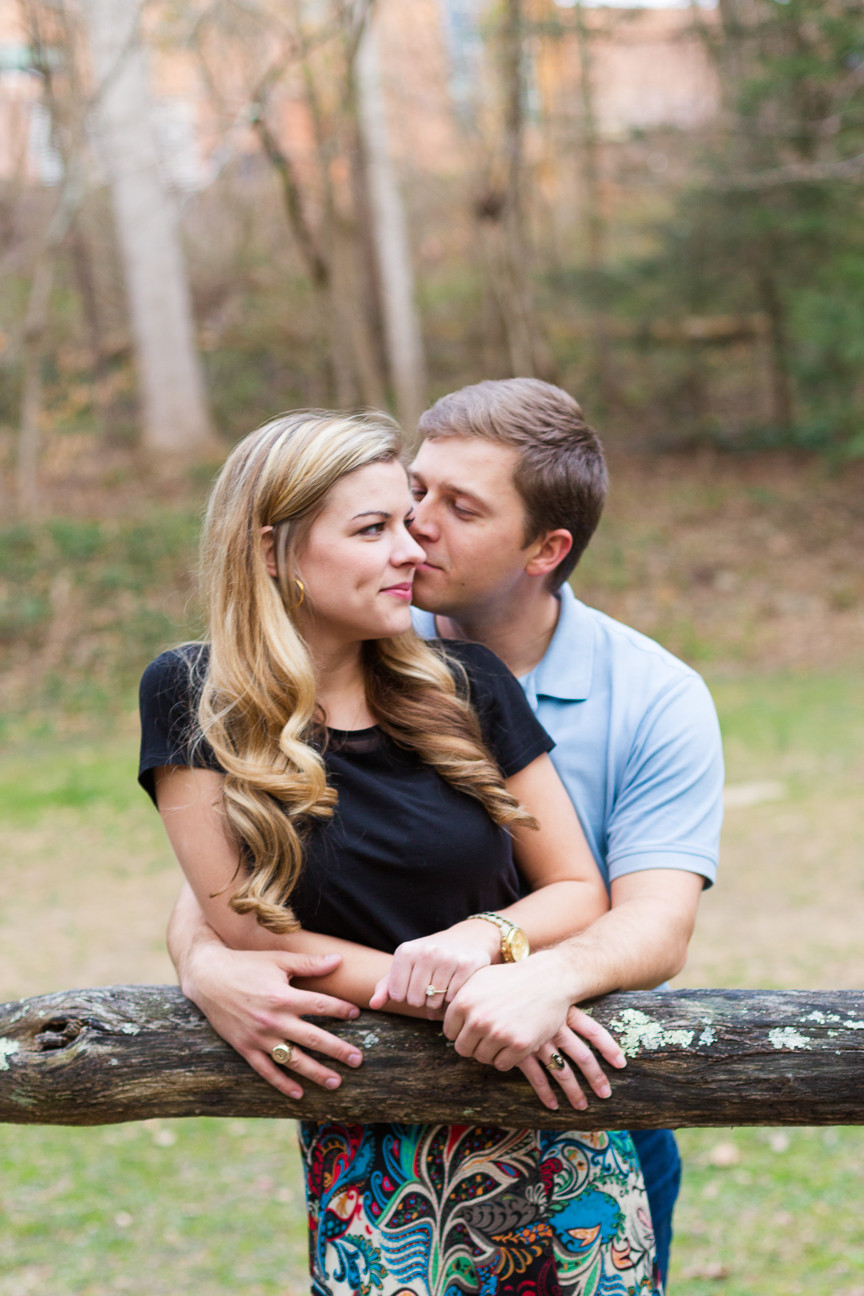 couple stands near fence, Asheville engagement session