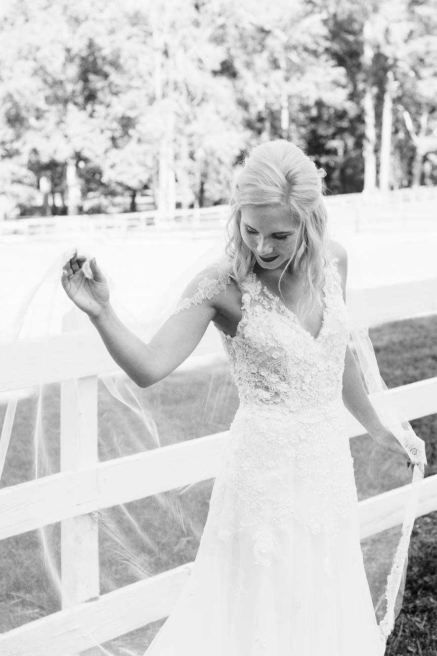 black adn white portrait of bride fixing her veil