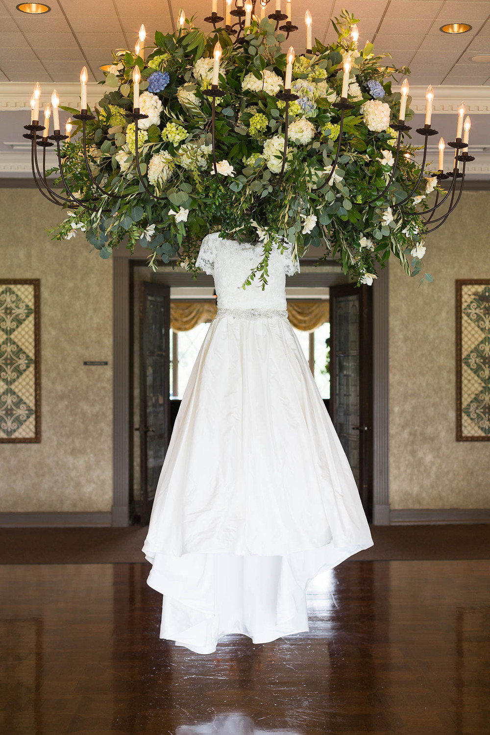brides wedding dress hangs on floral chandelier
