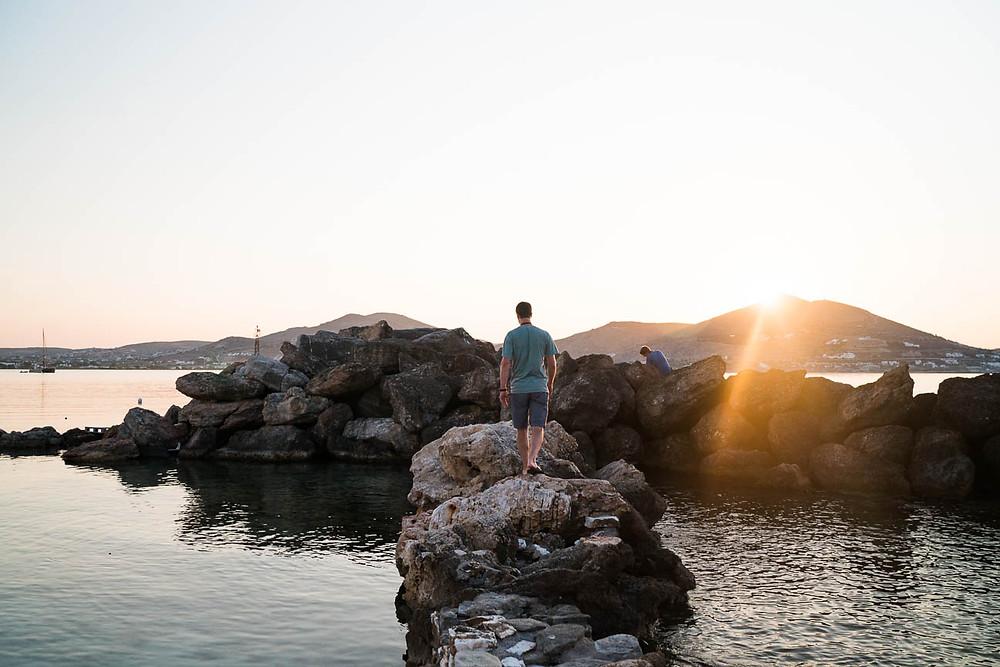 Man walks on rocks during sunset in Naoussa, Paros