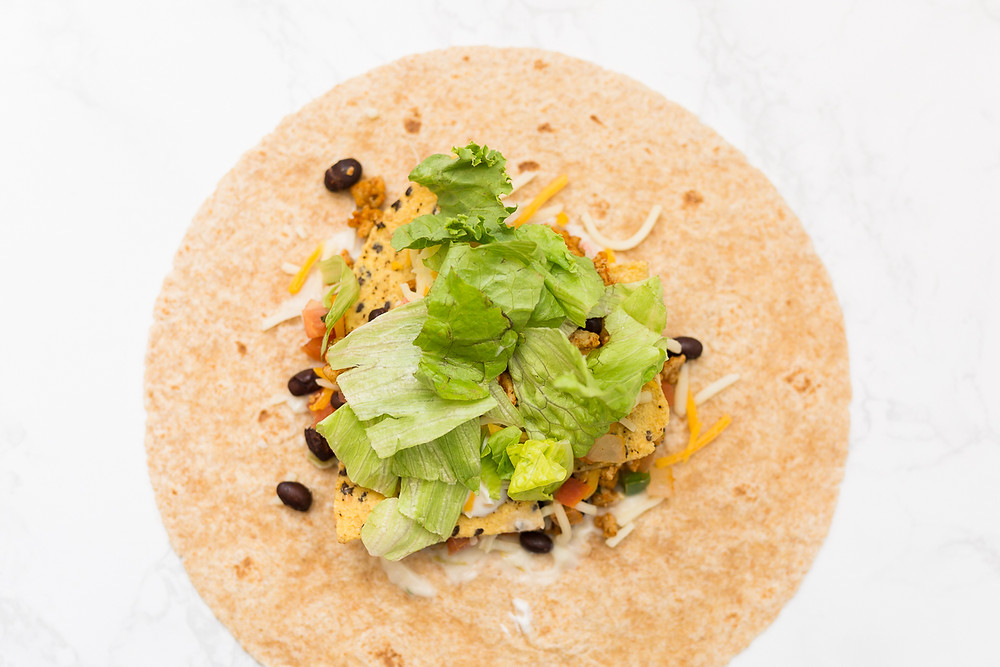 image of chicken, beans, and lettuce in a tortilla