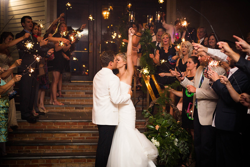 bride and groom kiss as guests cheer with sparklers