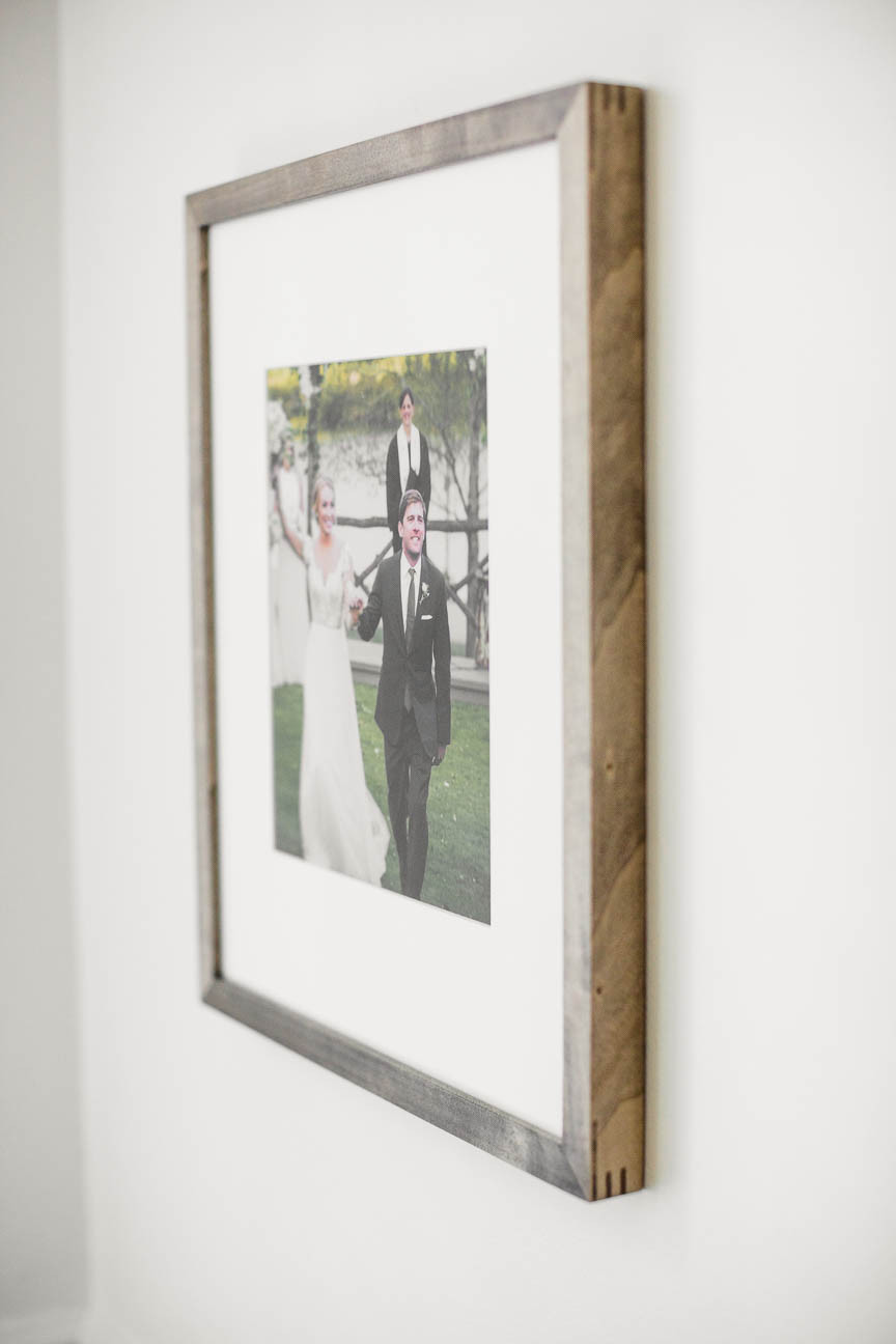 wood frame hanging on wall with wedding photo