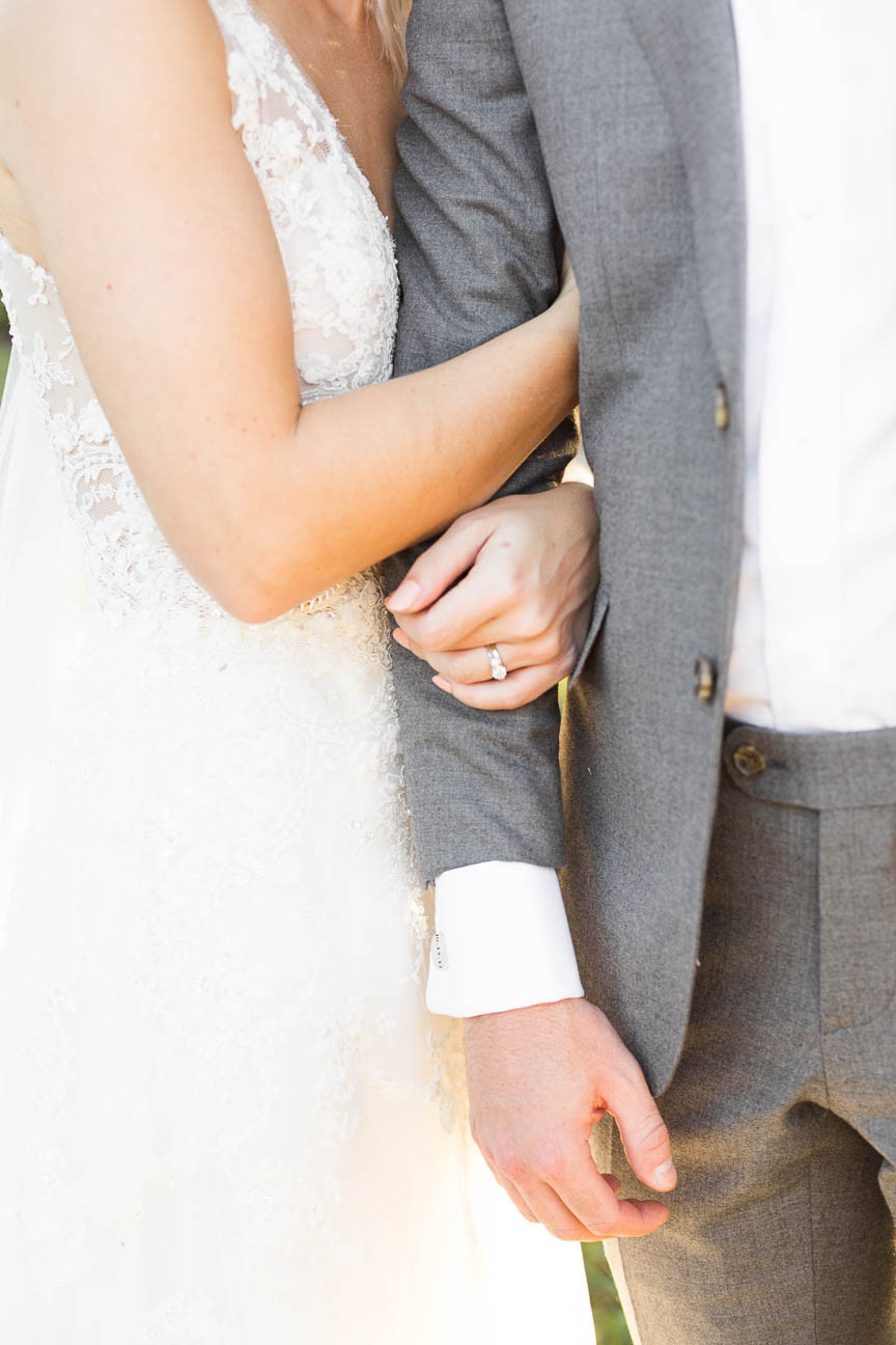 bride's rings as she hold's groom's arm