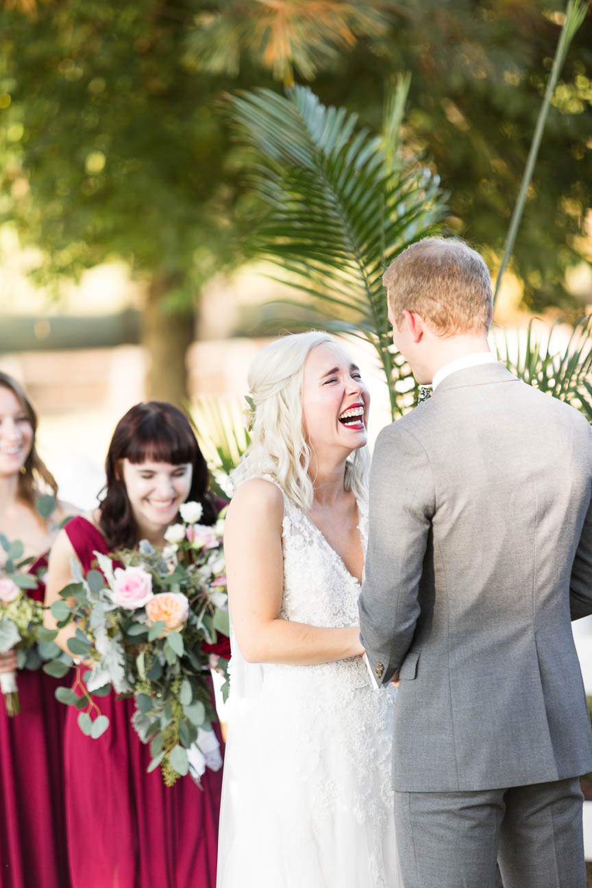 bride laughs with groom during ceremony
