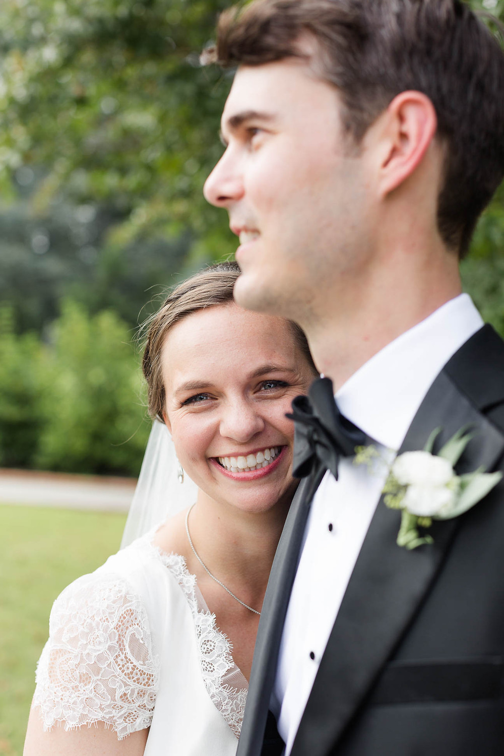 bride smiles while hugging the groom