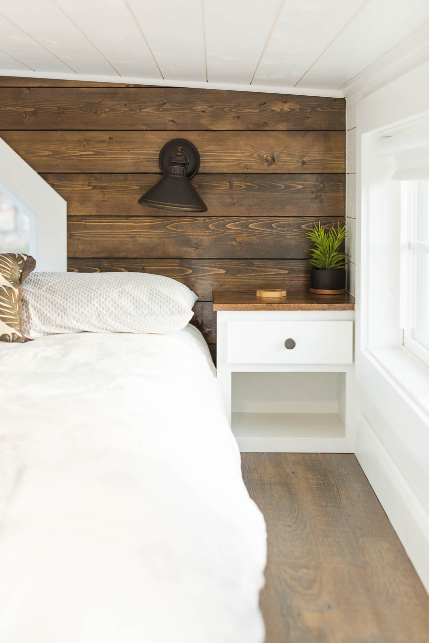 side table and bed in loft of tiny home