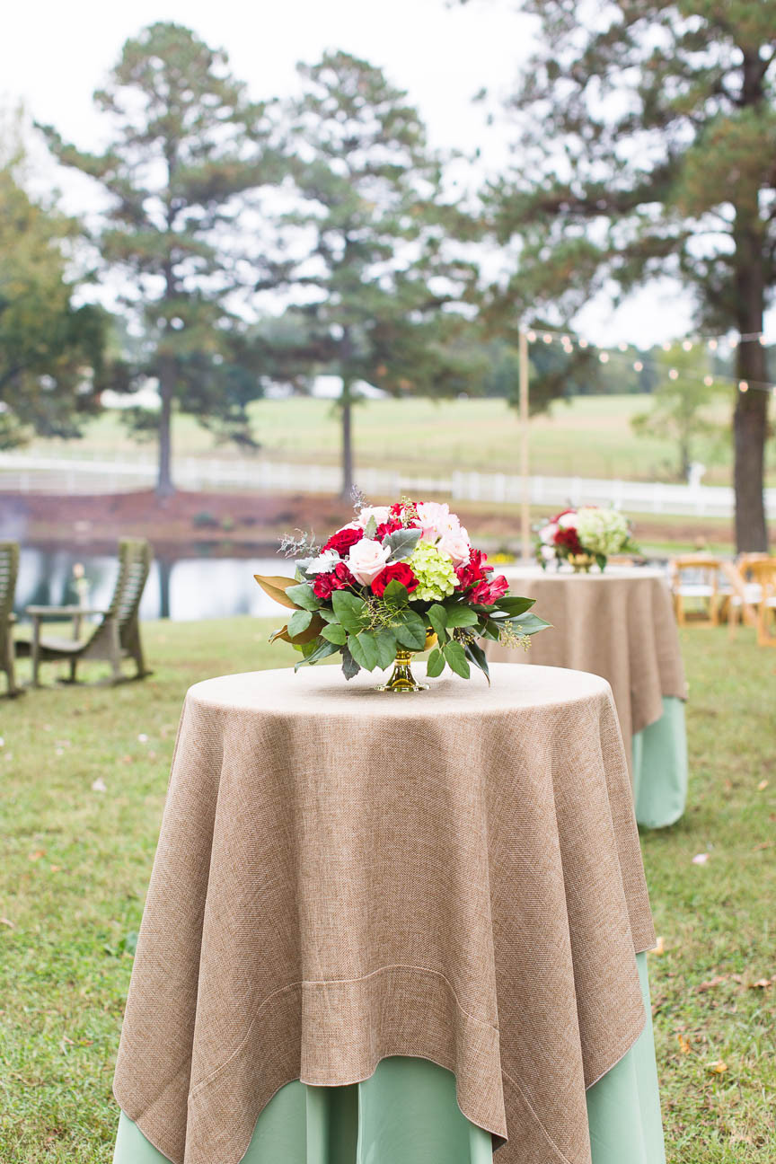 flowers on tables at reception in front of lake