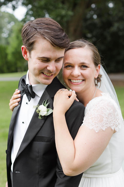 bride hugs her groom as he smiles down at her