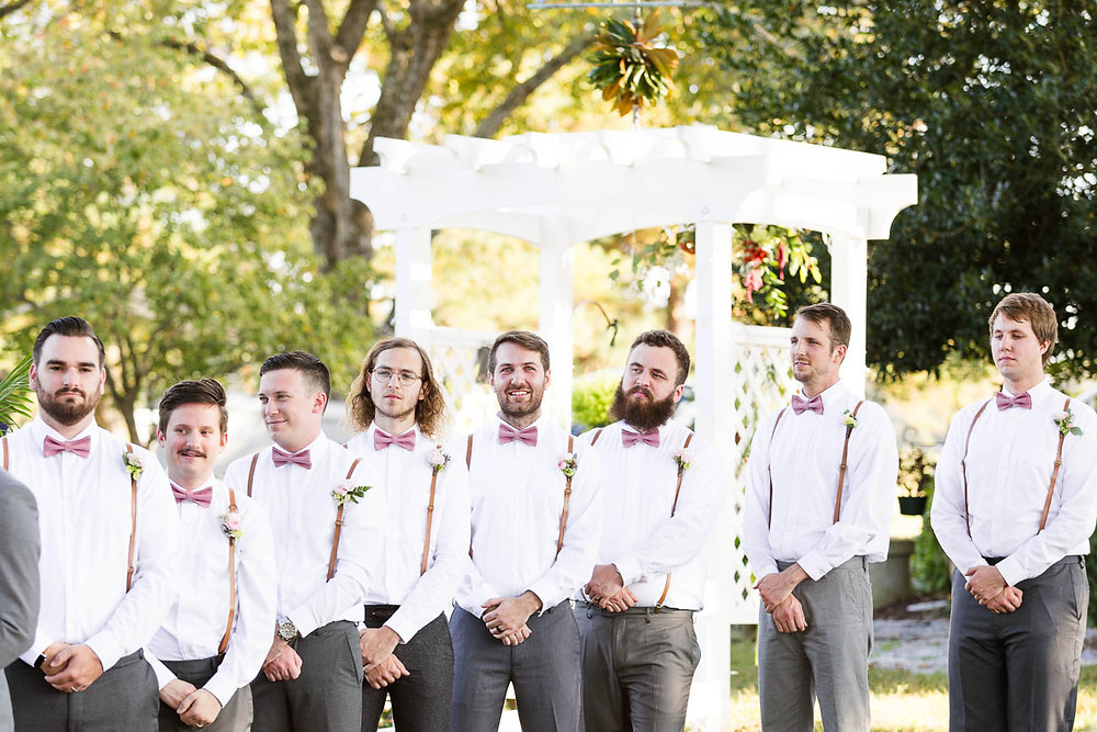 groomsmen lined up at ceremony wearing suspenders and pink bowties