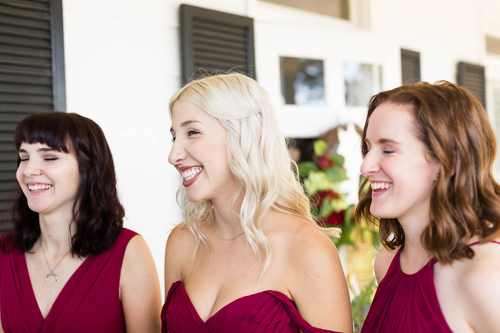bridesmaids smile as they see the bride in her dress