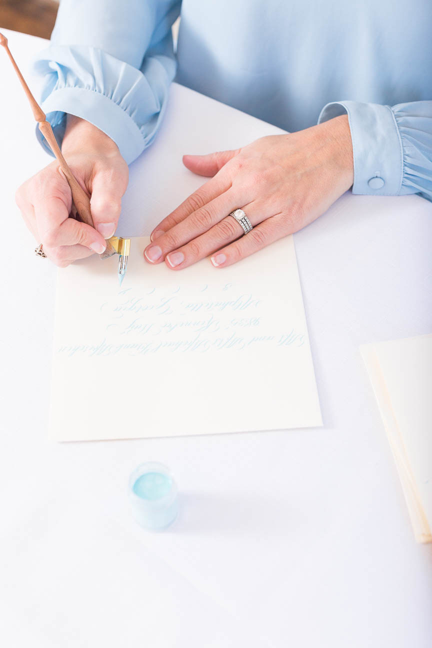 close up image of hands doing calligraphy on envelope