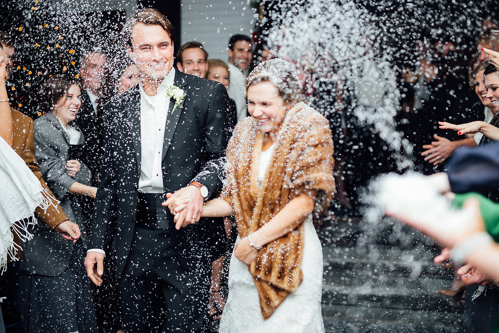 image of couple departing their wedding under white snow confetti