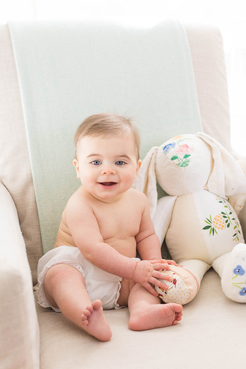 baby sits in chair with rabbit