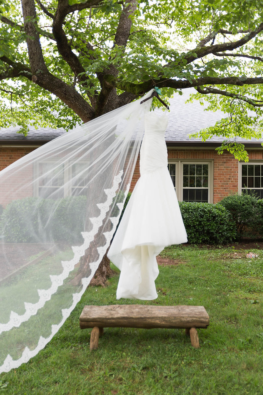 bride's gown hanging from tree with veil